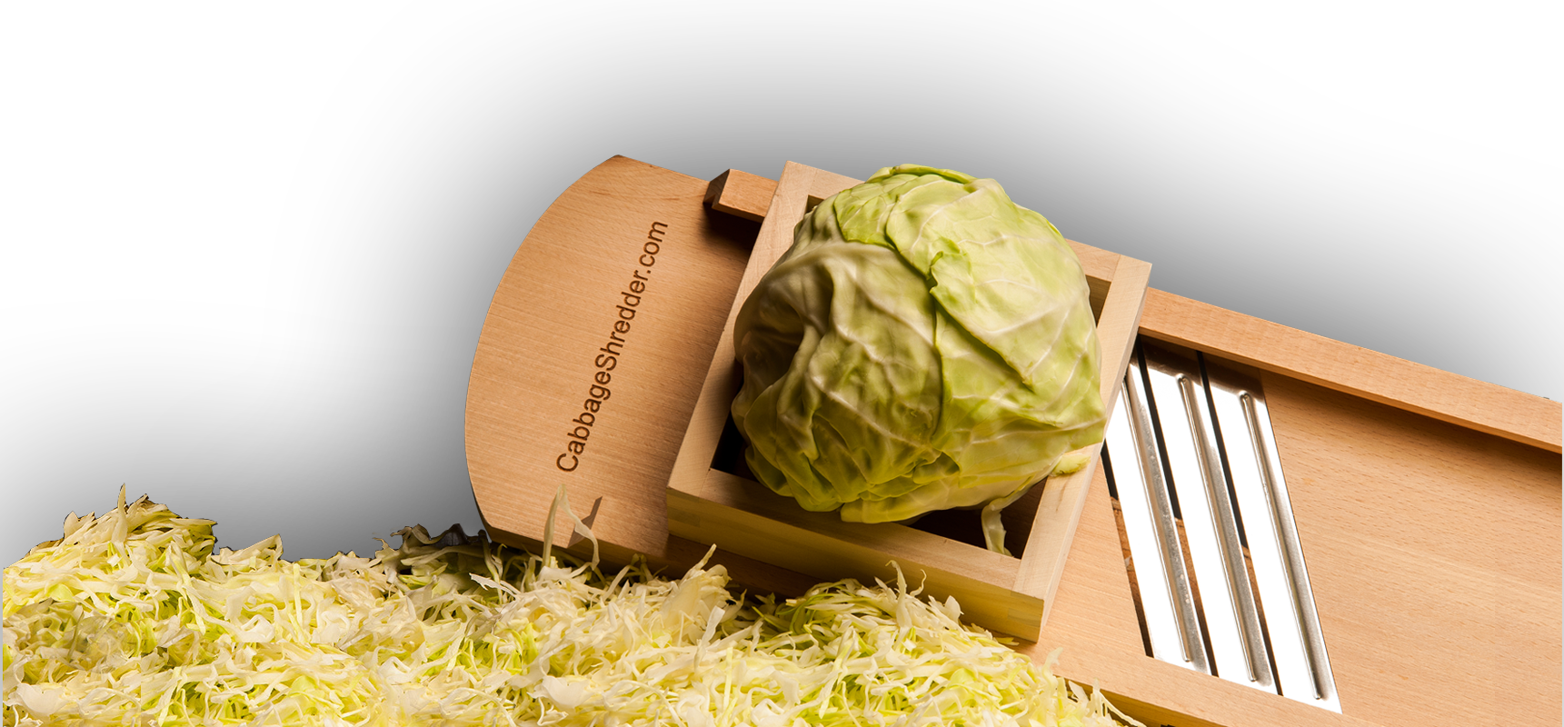 Large wooden cabbage shredder on a pile of finely shredded cabbage